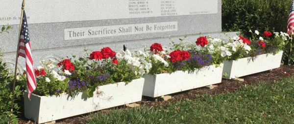 three white planter boxes filled with geraniums in front of veterans' memorial